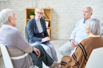Consultant with group of seniors sitting in a circle