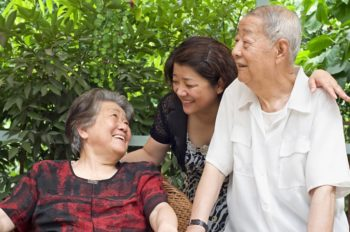Two happy senior parents with a younger caregiver daughter
