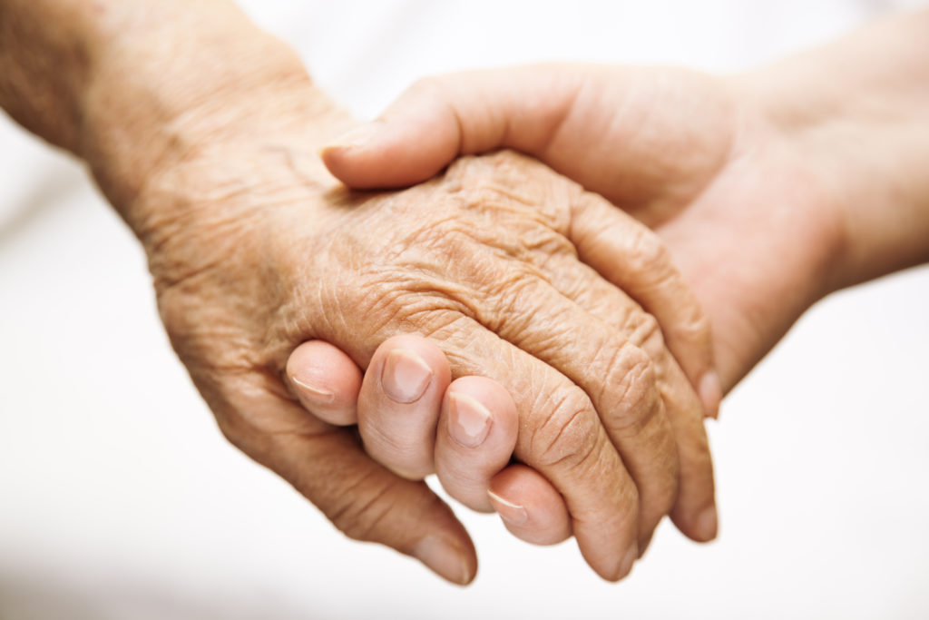Elderly hand being held by a younger hand